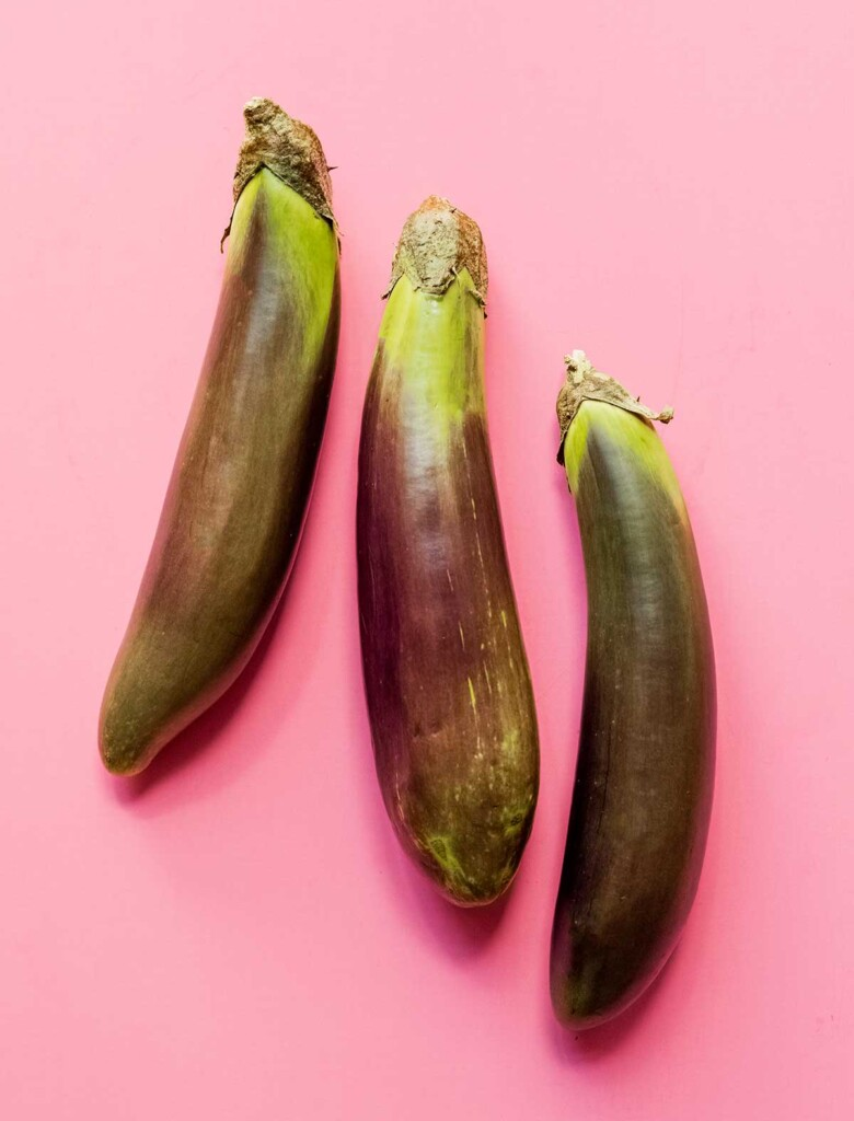 Three Filipino eggplants arranged in a row on a pink background