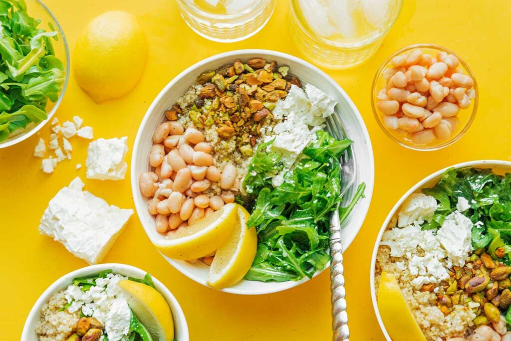 A lemony arugula grain bowl topped with pistachios, feta cheese, navy beans, and lemon dressing
