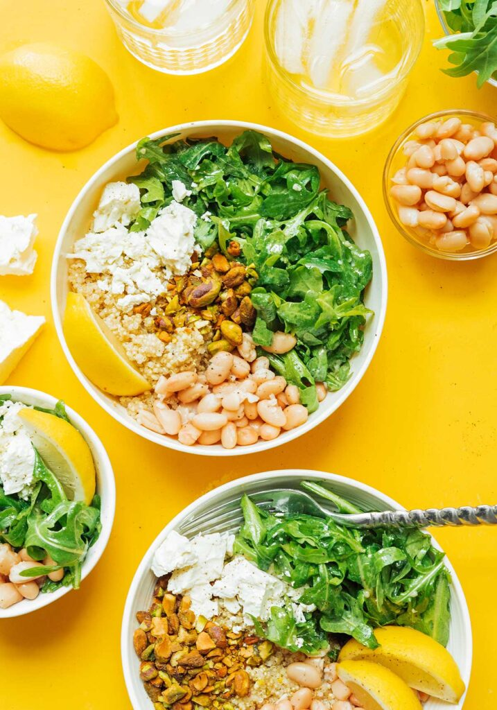 A arugula power bowl topped with pistachios, feta cheese, navy beans, and lemon dressing