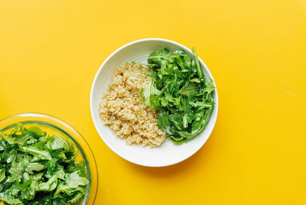 A white bowl filled with one serving of cooked quinoa and lemon dressed arugula