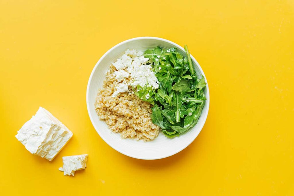 A white bowl filled with one serving of cooked quinoa, arugula, and feta cheese