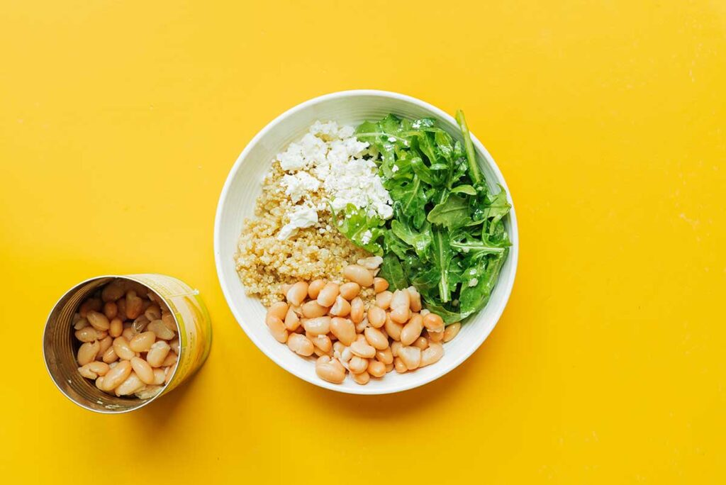 A white bowl filled with one serving of cooked quinoa, arugula, feta cheese, and navy beans