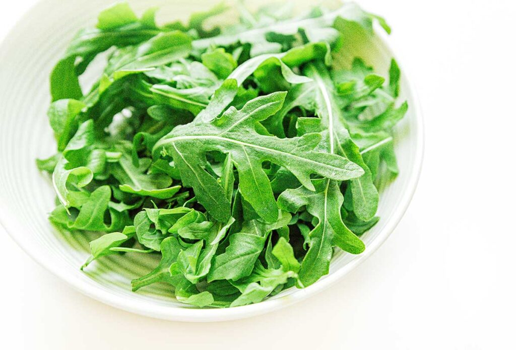 A while bowl filled with bright green arugula lettuce