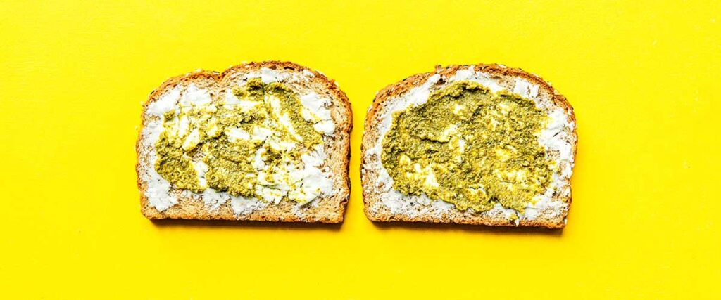 Two slices of bread lying open faced on a yellow background coated with layers of goat cheese and pesto