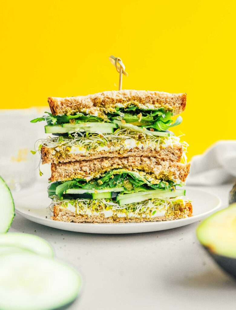 Two halves of an avocado sandwich stacked on a white plate and held with a toothpick