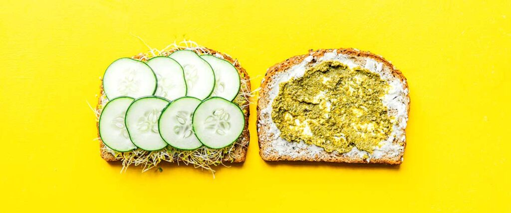 Two slices of bread lying open faced on a yellow background coated with layers of goat cheese, pesto, sprouts, and cucumber