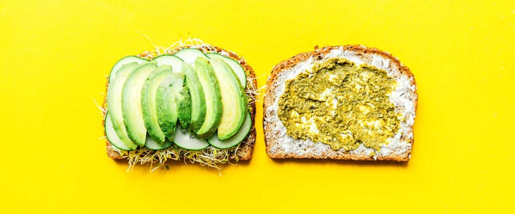 Two slices of bread lying open faced on a yellow background coated with layers of goat cheese, pesto, sprouts, cucumber, and avocado