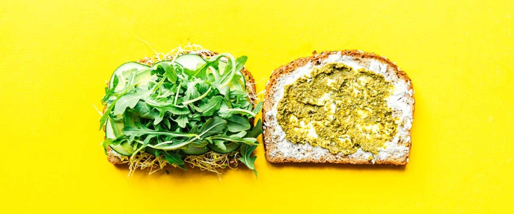 Two slices of bread lying open faced on a yellow background coated with layers of goat cheese, pesto, sprouts, cucumber, avocado, and arugula