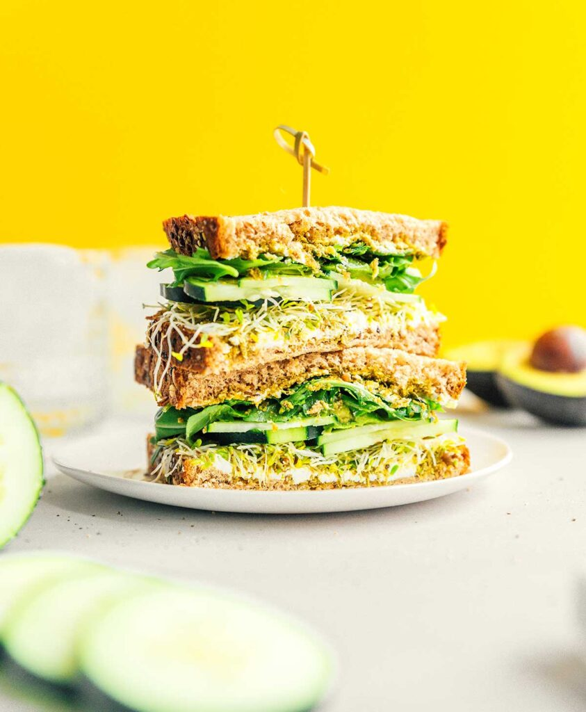 Two halves of a vegetarian sandwich stacked on a white plate and held with a toothpick