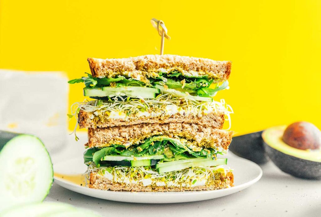 Two halves of an avocado veggie sandwich stacked on a white plate and held with a toothpick