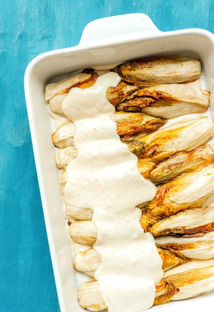 Layering Belgian endive gratin in a casserole dish with bechamel sauce