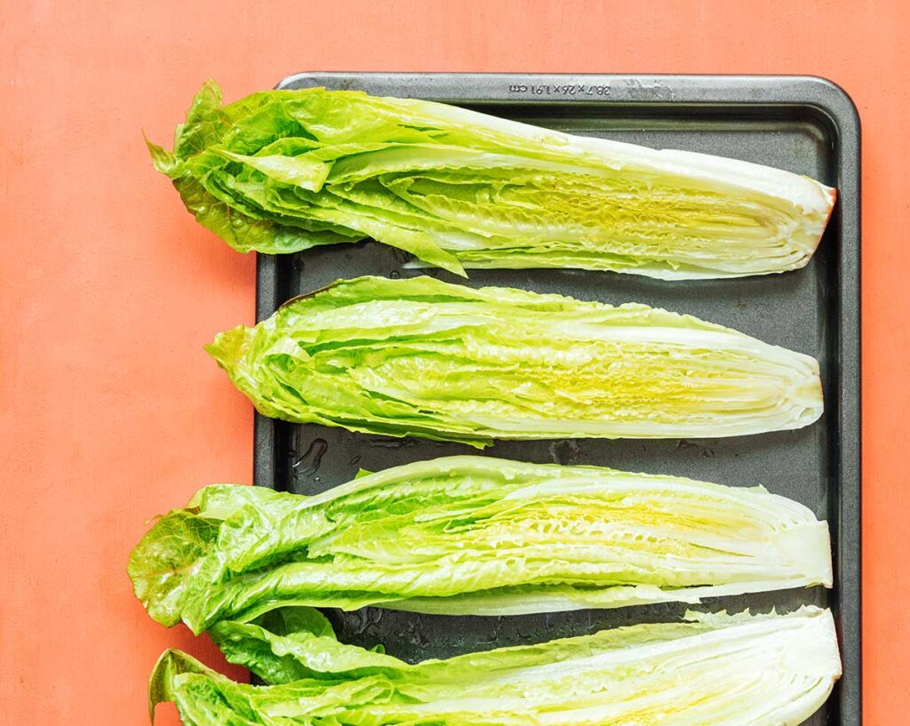 Four uncooked romaine heart halves lined up cut side-up on a baking tray