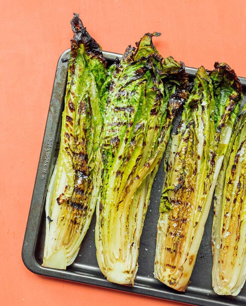 Four freshly grilled romaine heart halves lined up on a baking tray