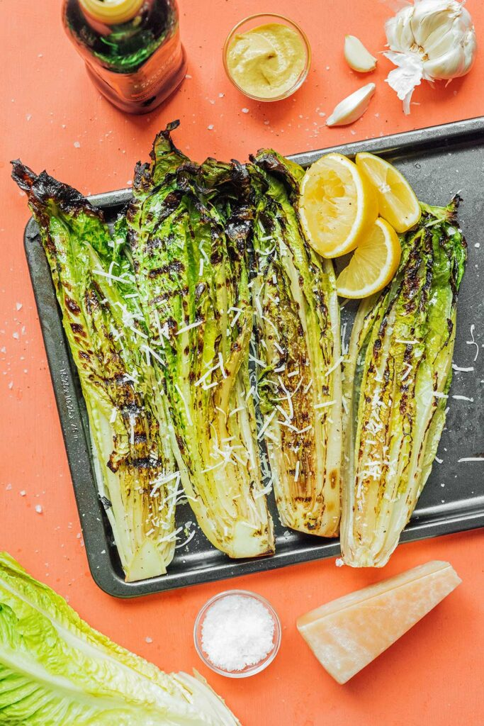 Four grilled romaine heart halves topped with parmesan cheese sitting atop a baking sheet next to lemon slices