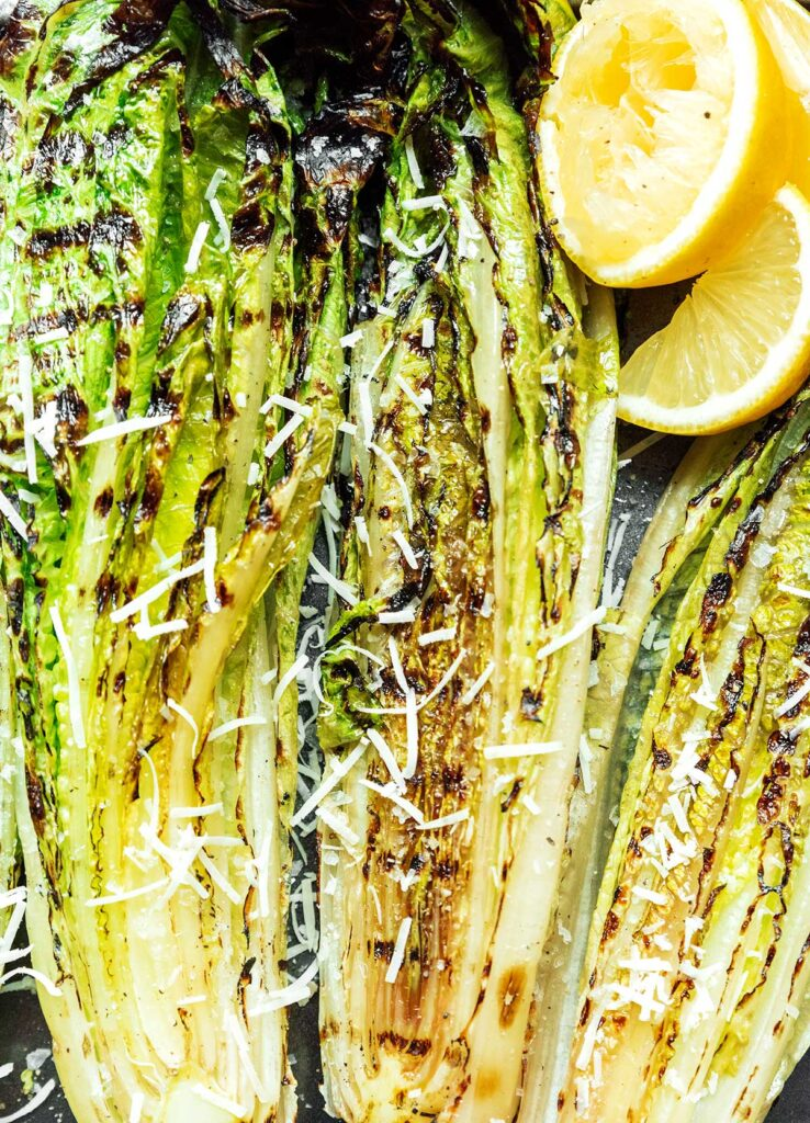 A close up view detailing the texture of grilled romaine hearts topped with parmesan cheese