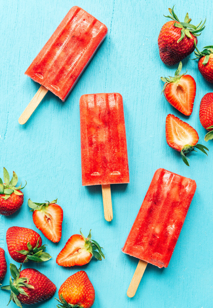 Red strawberry Mexican paletas on a blue background