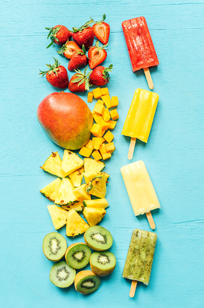 Multiple colors of fruit paletas on a blue background