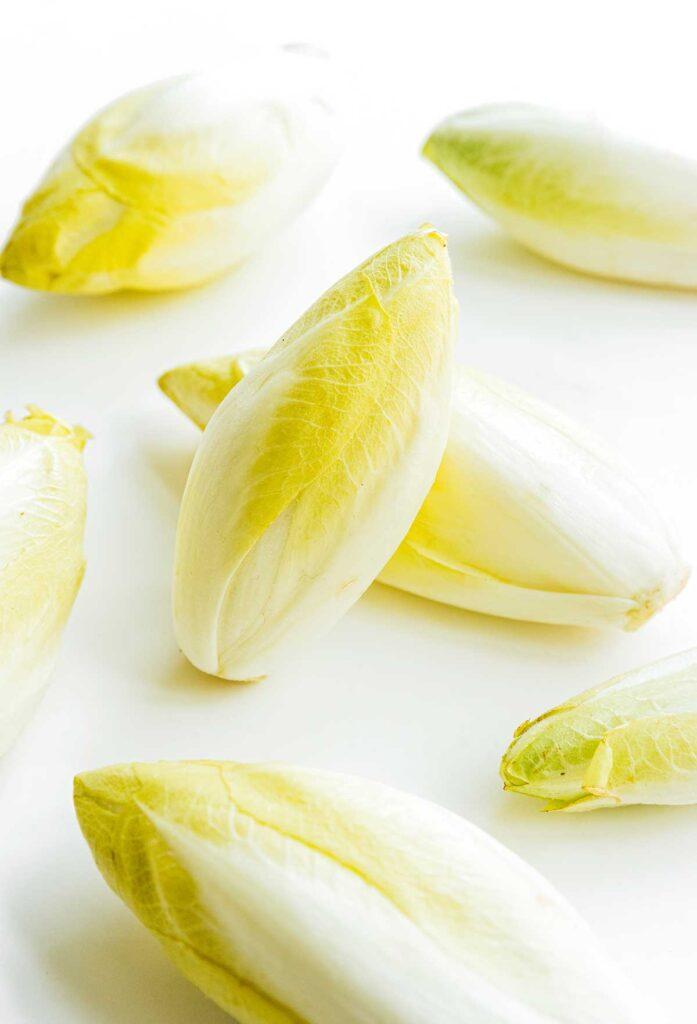 Seven light yellow endives arranged on a white background