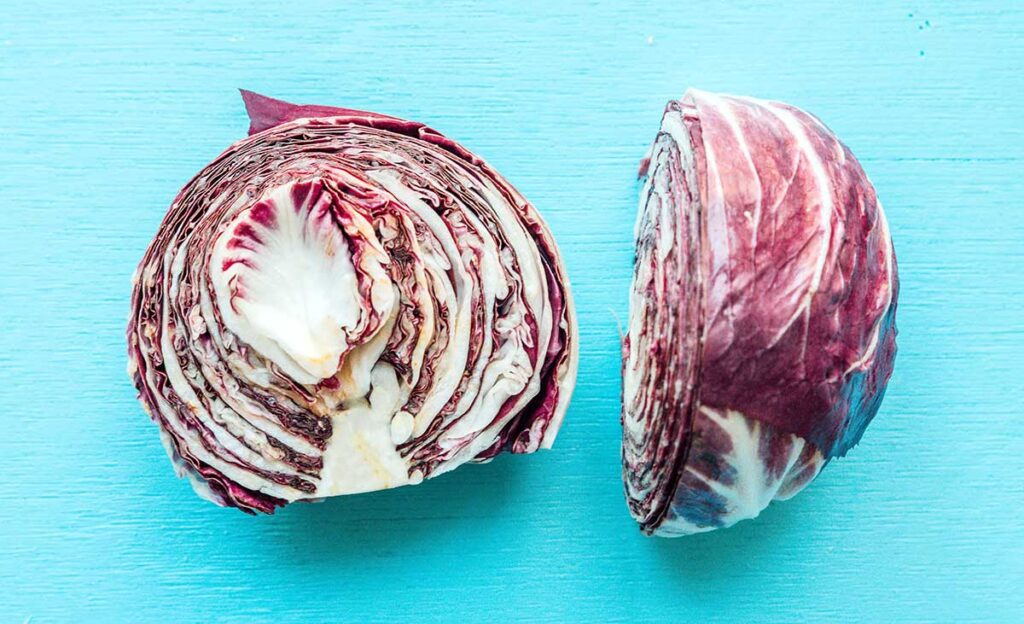 A head of radicchio pasta sliced in half and laid on a blue background