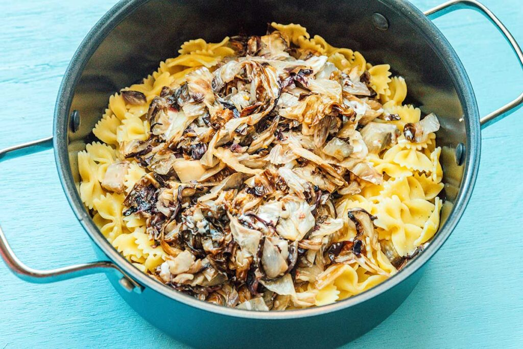A pot filled with pasta, radicchio lettuce, and goat cheese