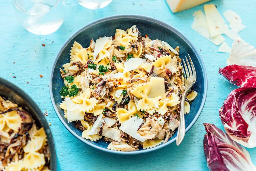 A blue bowl filled with radicchio pasta with goat cheese