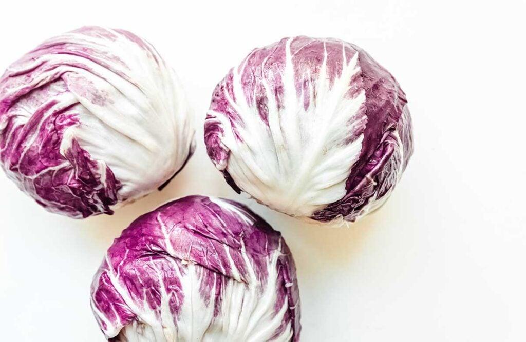 Three heads of purple radicchio lettuce on a white background