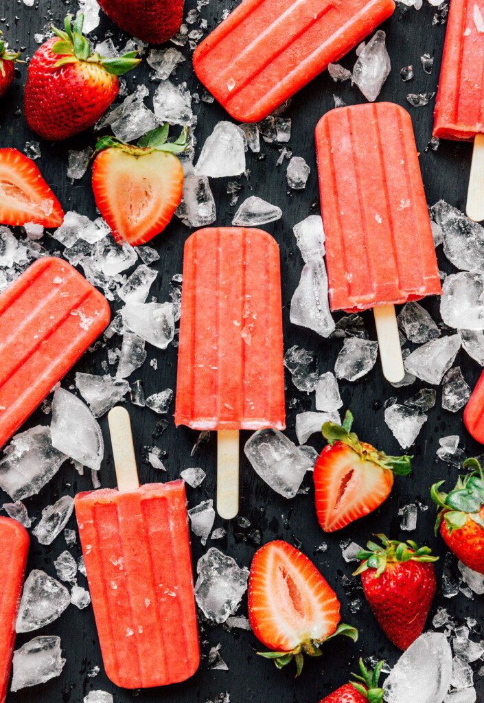 Real strawberry popsicles displayed on a black background and surrounded by ice and strawberries