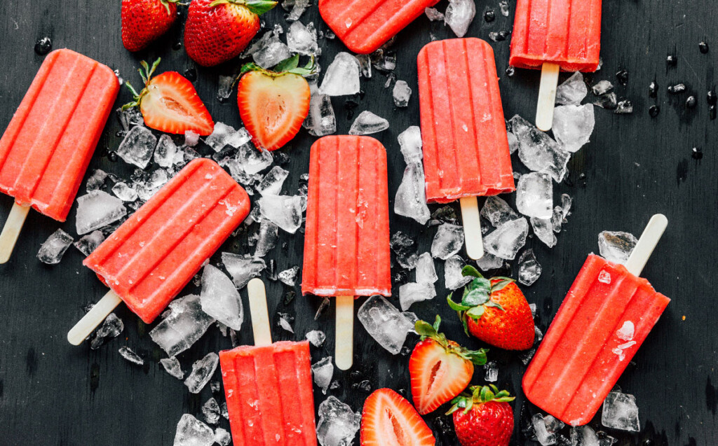 Sugar-free strawberry popsicles displayed on a black background and surrounded by ice and strawberries