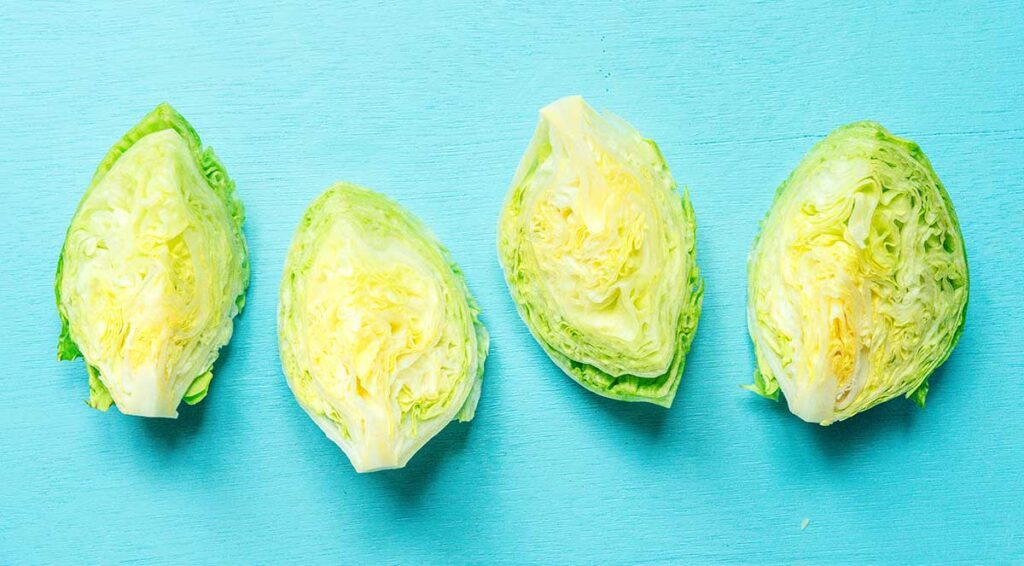Four quarters of a head of iceberg lettuce lined up on a blue background