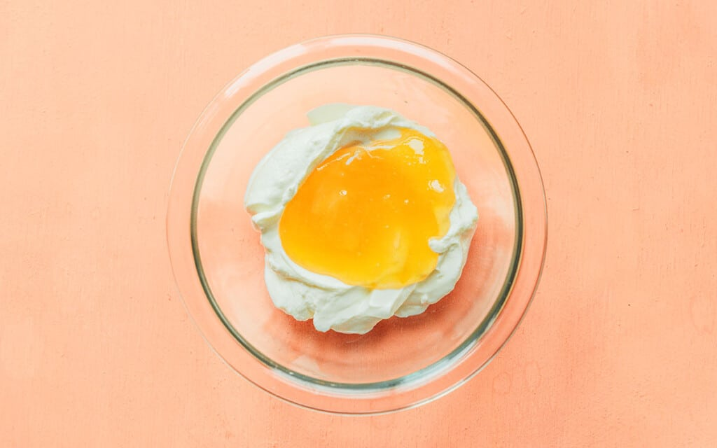 A clear glass bowl filled with Greek yogurt and honey