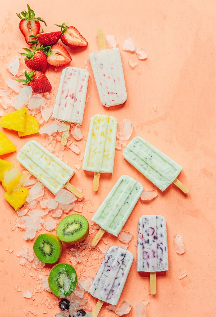 Various 3 ingredient fruit and yogurt popsicles arranged on an orange background and surrounded by ice, strawberries, pineapple, kiwis, and blueberries