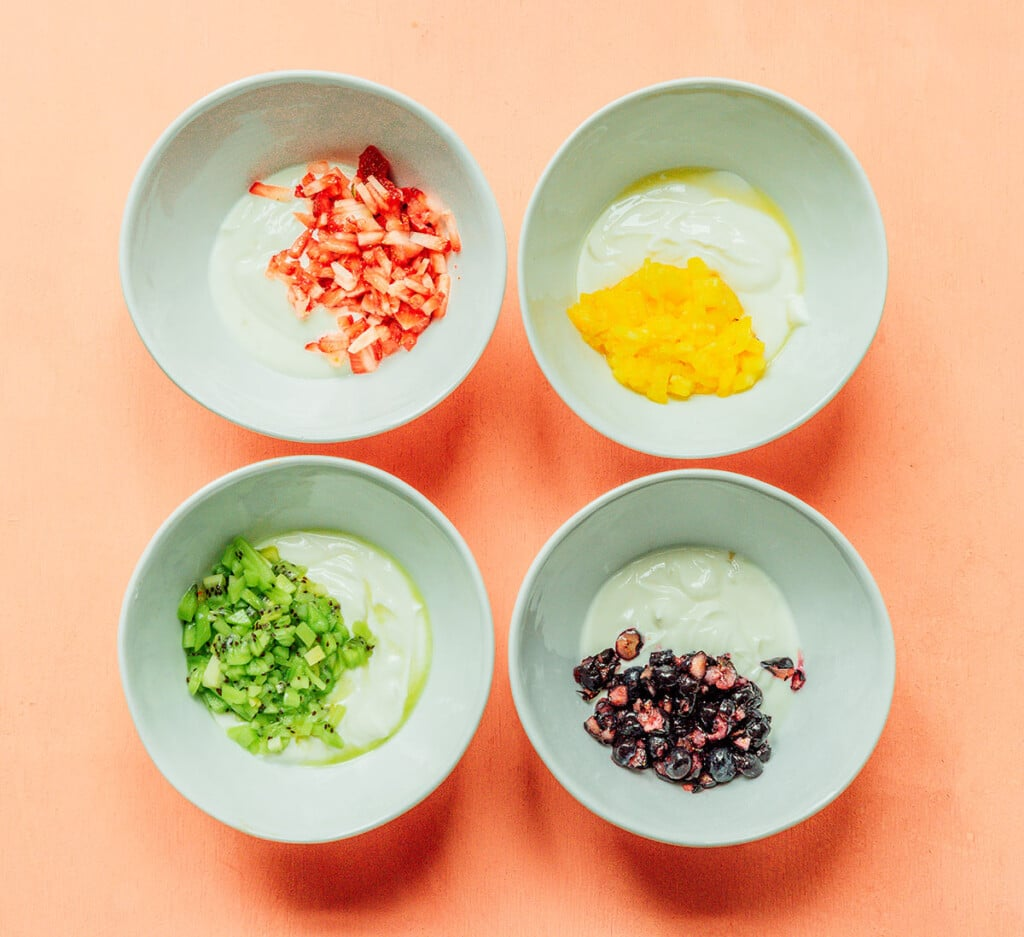 Four bowls arranged in a square, each one filled with ingredients for a different popsicle flavor