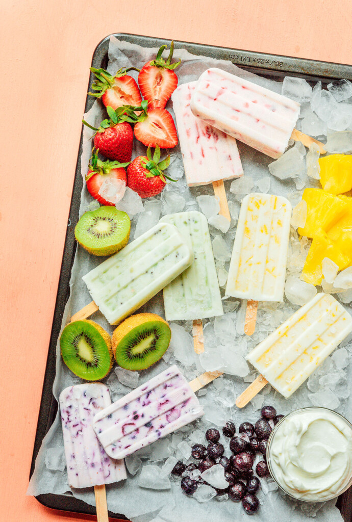 Various 3 ingredient fruit and yogurt popsicles arranged on a tray surrounded by ice, strawberries, pineapple, kiwis, and blueberries