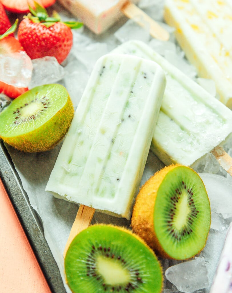 A close up shot detailing the texture and colors of kiwi and yogurt popsicles