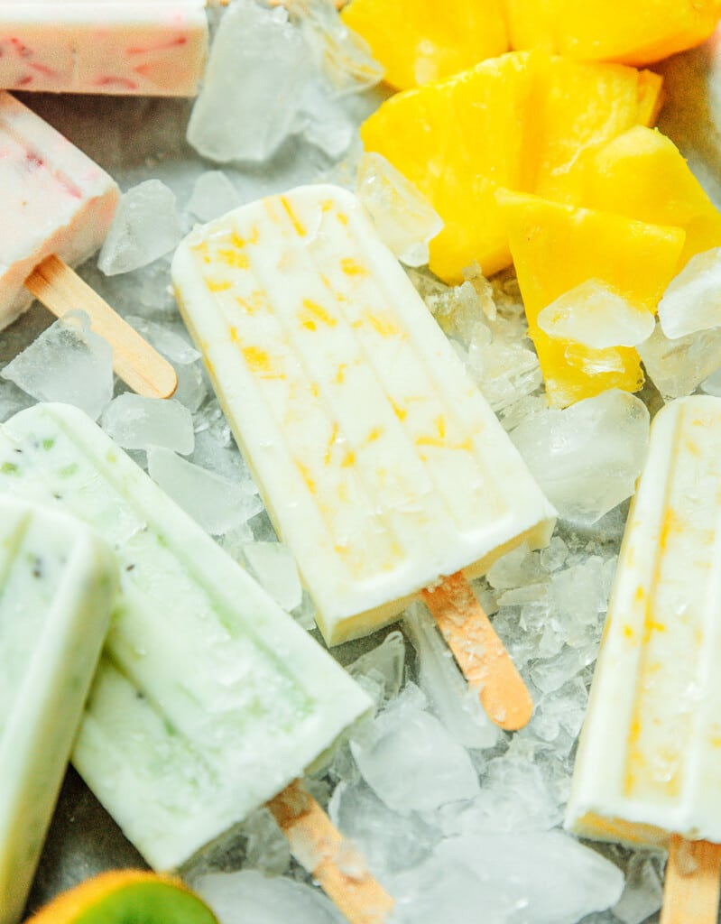 A close up shot detailing the texture and colors of pineapple and yogurt popsicles