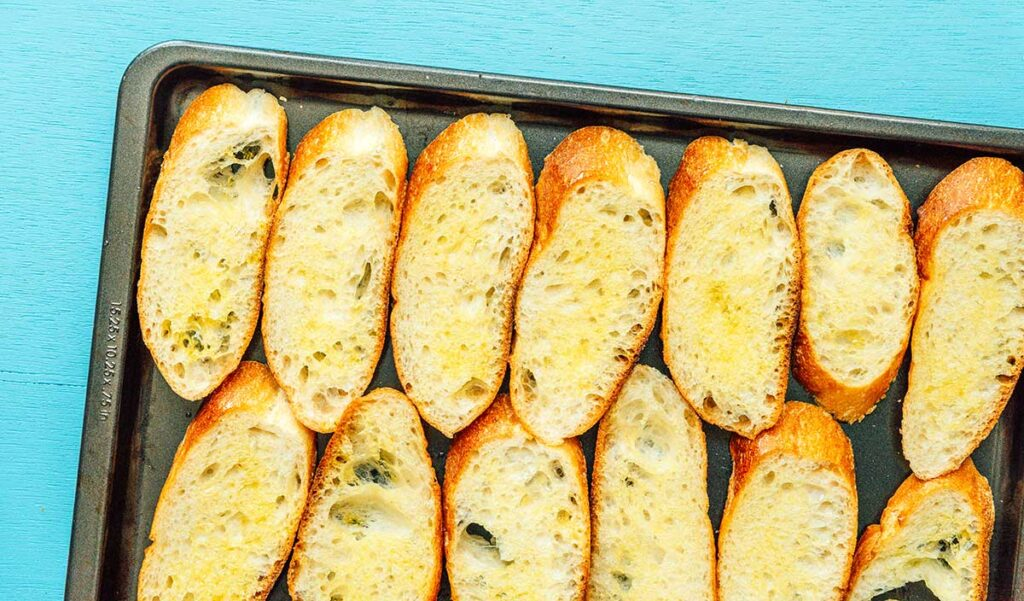 13 baguette slices on a baking tray and drizzled with olive oil