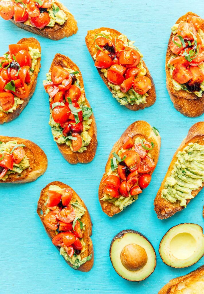 Pieces of assembled avocado and tomato bruschetta scattered around on a blue background