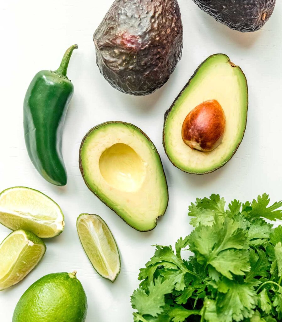 A bird's eye view of some avocados, lime wedges, a jalapeño, and a bunch of cilantro