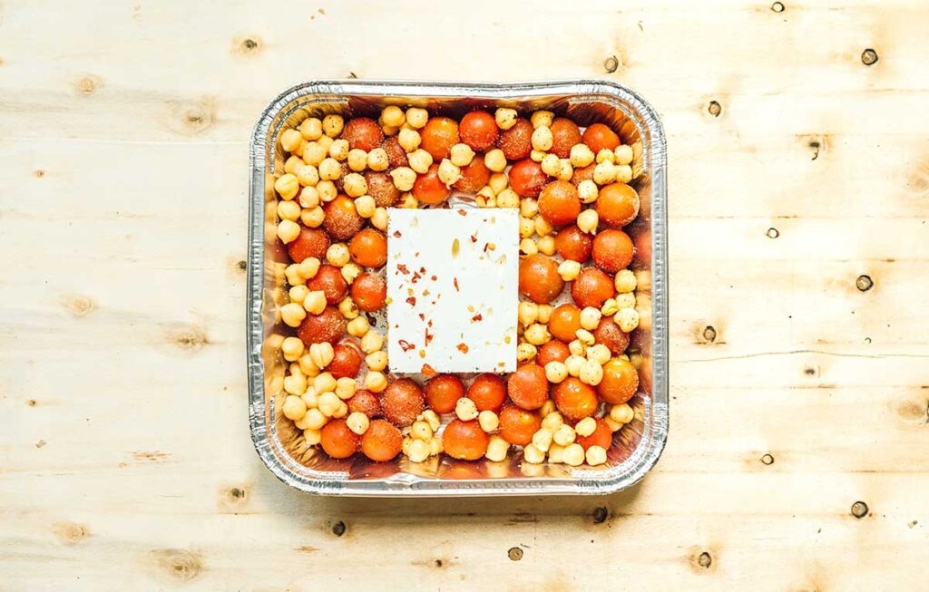 An 8x8 aluminum tray filled with prepared campfire tomato feta bake ingredients