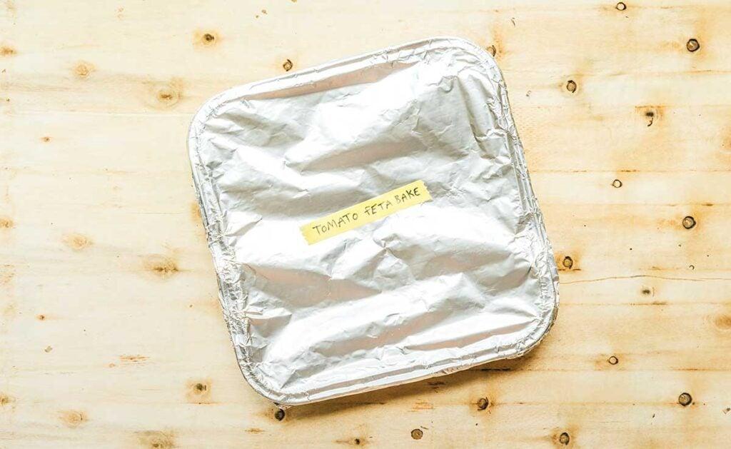 "An aluminum 8x8 dish filled with tomato feta bake, covered with aluminum foil, and labeled ""tomato feta bake"""