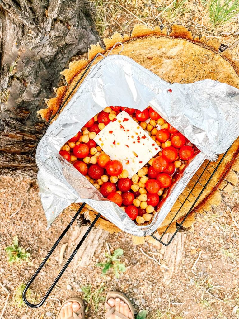 A tray of freshly cooked campfire feta bake on top of a tree stump