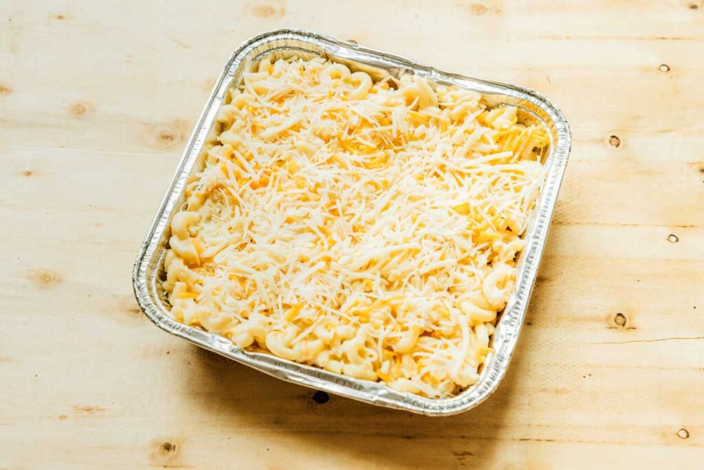 An aluminum tin filled with prepped campfire mac n cheese