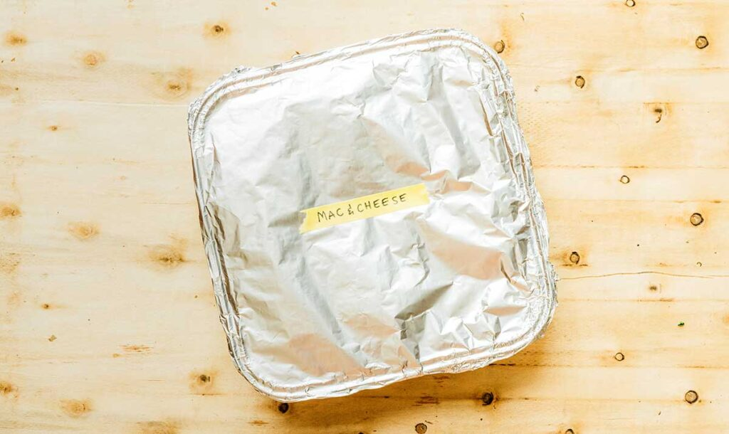 """An aluminum container filled with campfire mac and cheese, covered with tin foil, and labeled """"mac & cheese"""""""
