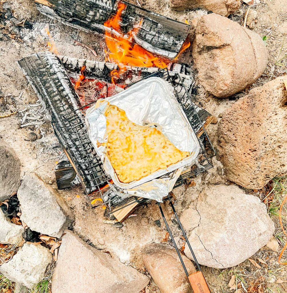 Cooking a disposable aluminum container of campfire mac n cheese on logs over a campfire