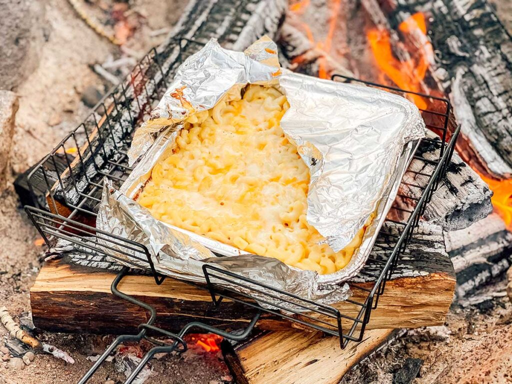 Cooking a disposable aluminum container of campfire mac and cheese on logs over a campfire