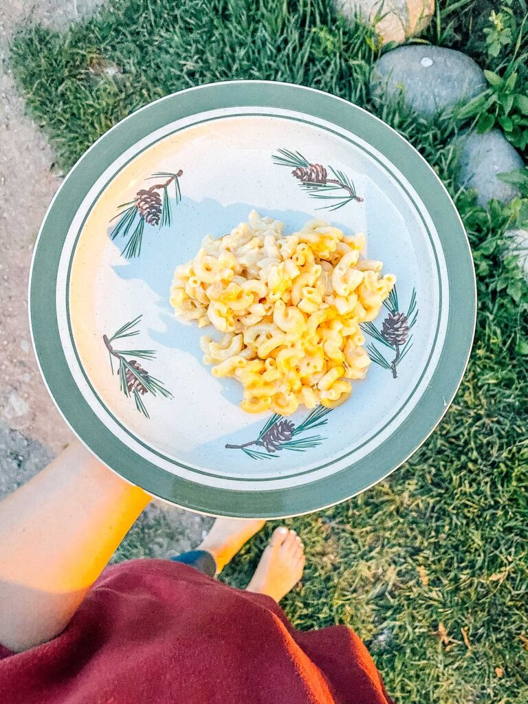 Holding a plate with a serving of campfire mac and cheese