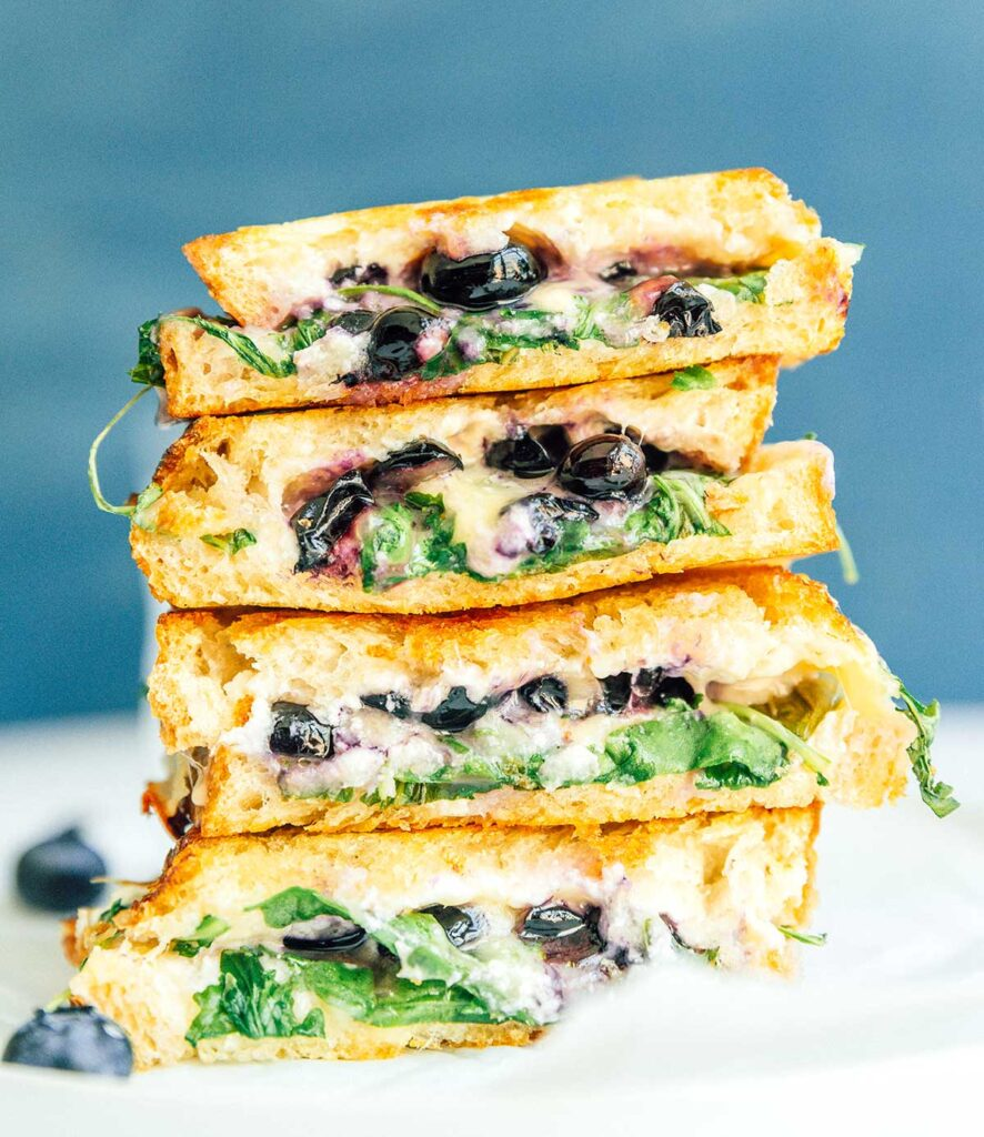 Four blueberry grilled cheese sandwich halves stacked on top of one another