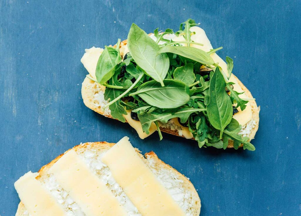 One piece of sourdough bread topped with goat cheese, a slice of mozzarella, halved blueberries, and arugula beside a second piece of bread topped with goat cheese and mozzarella