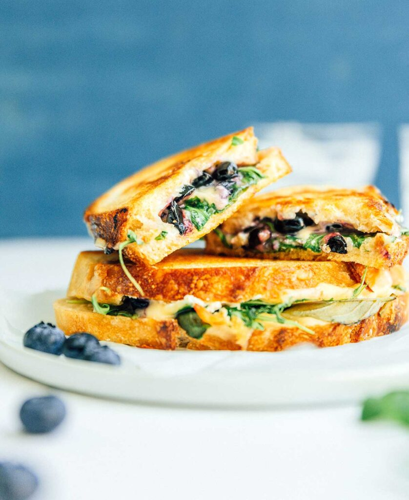 Two blueberry grilled cheese sandwiches on a plate, with one sandwich cut in half and stacked on top of the other