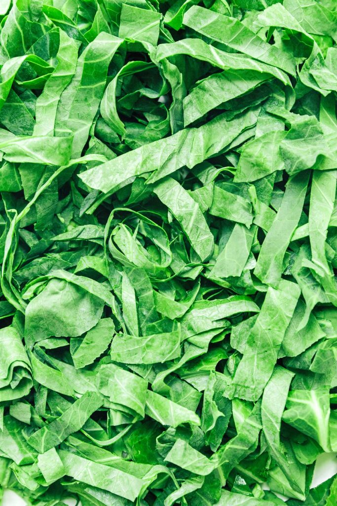 A close up view detailing the texture of sliced collard green leaves